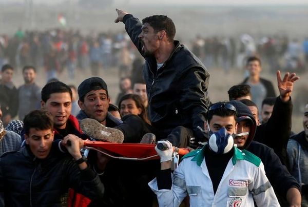A wounded Palestinian shouts as he is evacuated during clashes with Israeli troops at a protest near