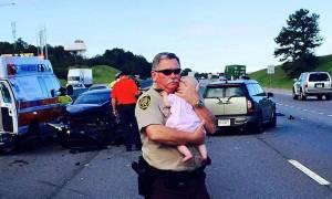 Αστυνομικός παρηγορεί βρέφος μετά από αυτοκινητιστικό ατύχημα