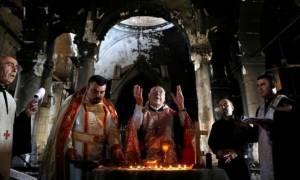 Ιράκ: Σε μια μισοκαμένη εκκλησία κοντά στη Μοσούλη προσεύχονται και πάλι οι χριστιανοί (pics)