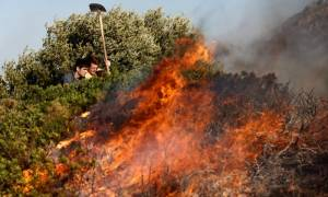 One house torched in wildfire still burning western Achaia