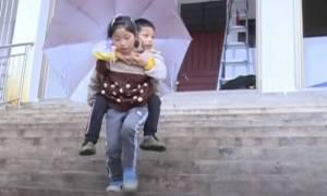 Η ιστορία της Zhou: Το κορίτσι που κουβαλά κάθε μέρα τον ανάπηρο αδελφό της στο σχολείο
